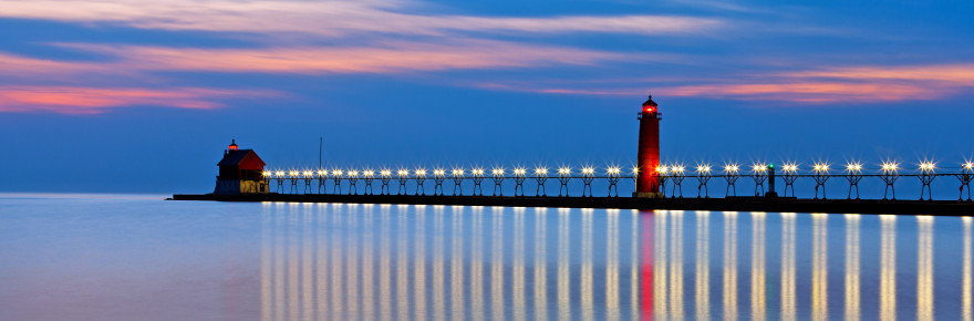 The lights strung along the catwalk twinkle like stars on the Grand Haven Pier at night. The catwalk runs between the inner light and outer light in Grand Haven Michigan.